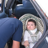 Firefighter performing a child safety seat inspection