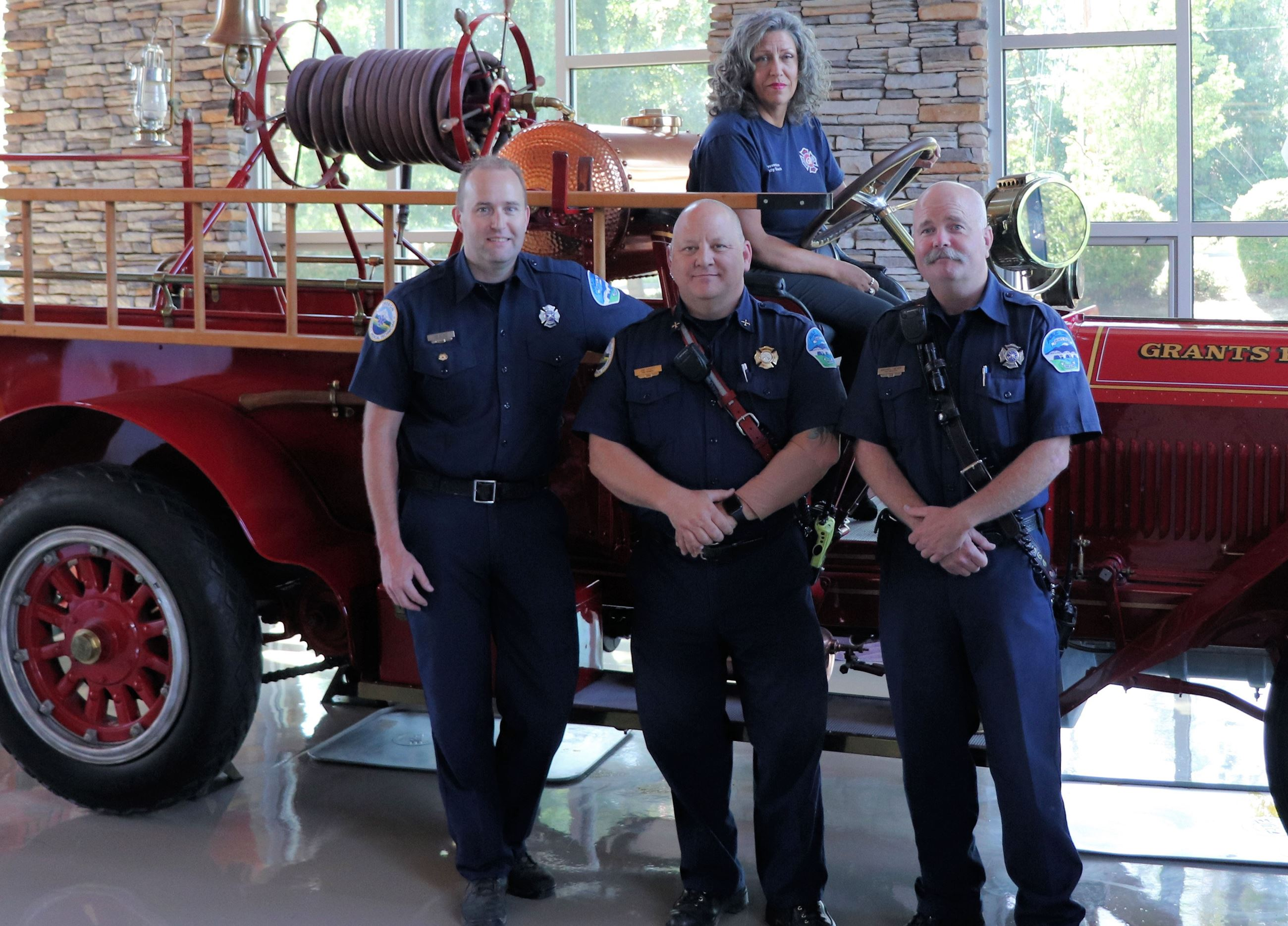Fire Prevention Team in front of old red fire truck with Office Assistant in drivers seat